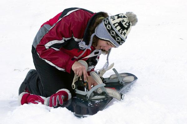 Ремонтирует крепление сноуборда